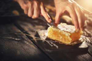 Fresh honeycomb just from beehive being sliced on a wooden table.