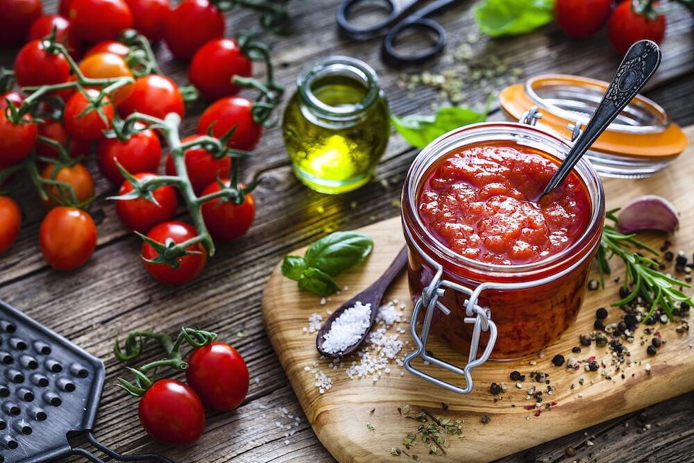 homemade tomato sauce in a glass jar shot on rustic kitchen table. Fresh ripe tomatoes, basil, rosemary, olive oil, peppercorns and salt are all around the tomato sauce jar.