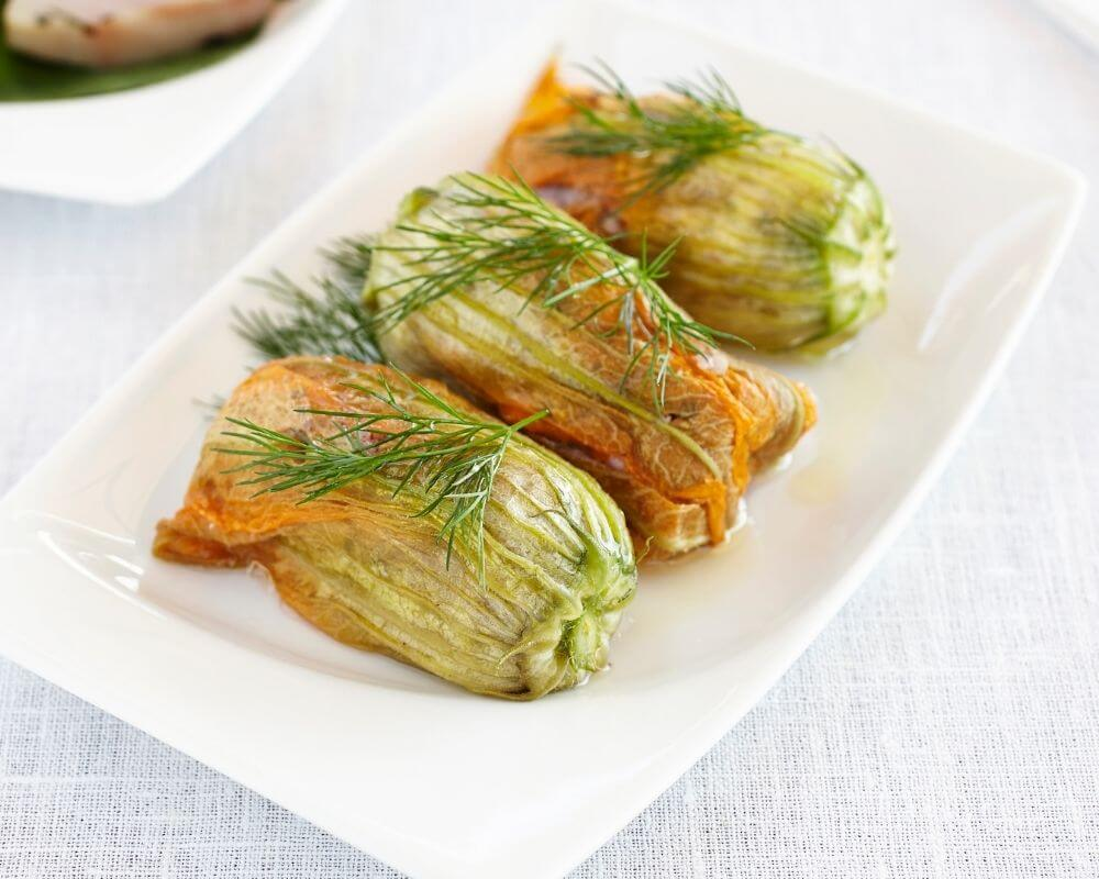 Sauteed squash blossoms on a plate garnished with dill.