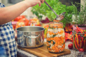 Young women preserving fresh organic cauliflower,carrots and garlic in jars at home