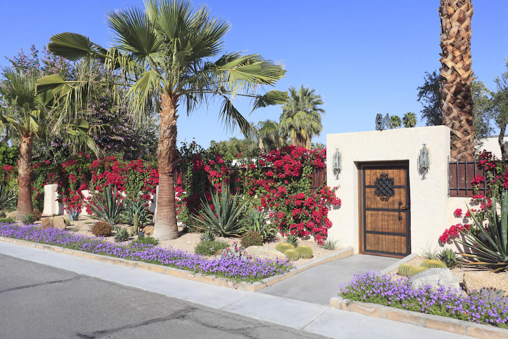 Desert landscaping in front of a Spanish style house.