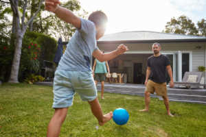 Child kicking ball with parents in the yard