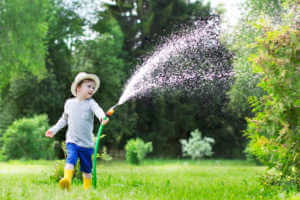 Child watering lawn with hose.