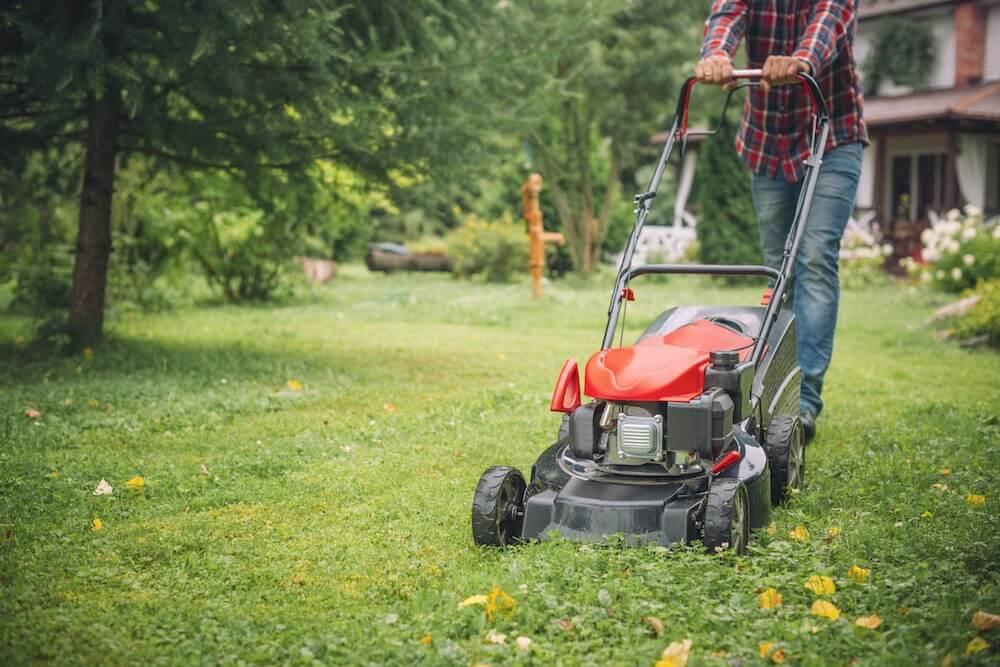 Man mowing grass near his house
