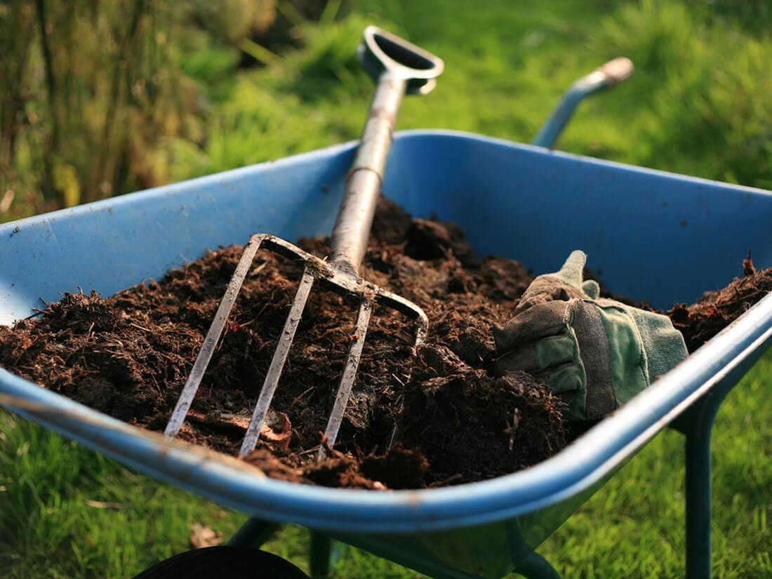 Pitchfork and dirt in wheelbarrow