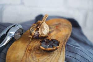 Black garlic halves on board