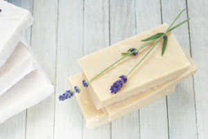 hand made soap with lavender flowers on white wooden background