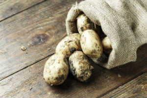 Potatoes spilling out of a burlap sac onto a dark wood surface.