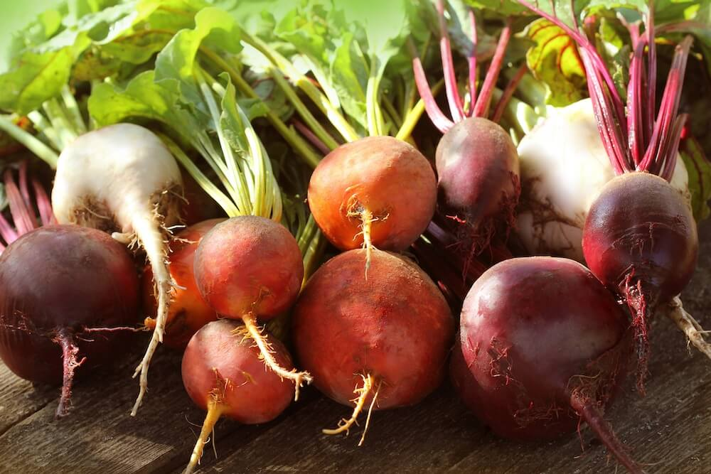 Red, golden, white beet on a wooden table