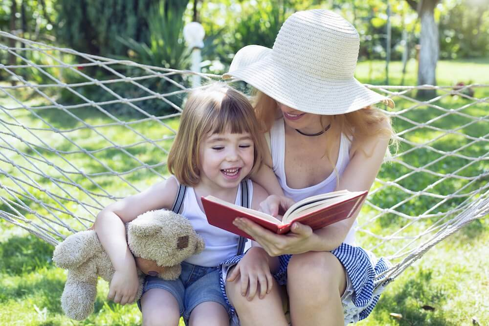 child and parent having fun and reading a book on hammock.