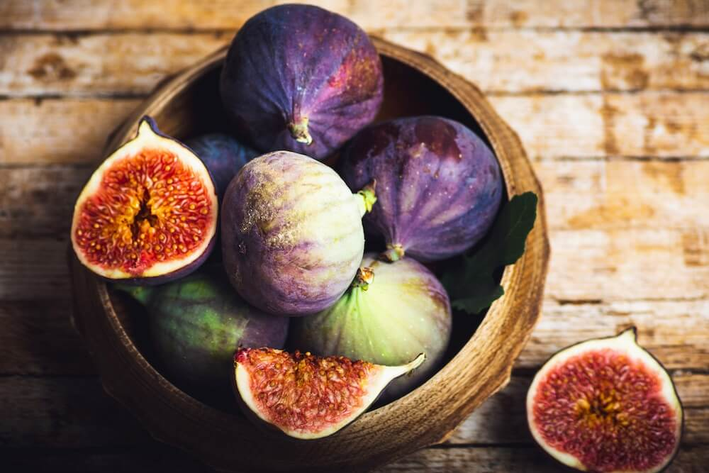 purple fresh figs slices on a wooden table