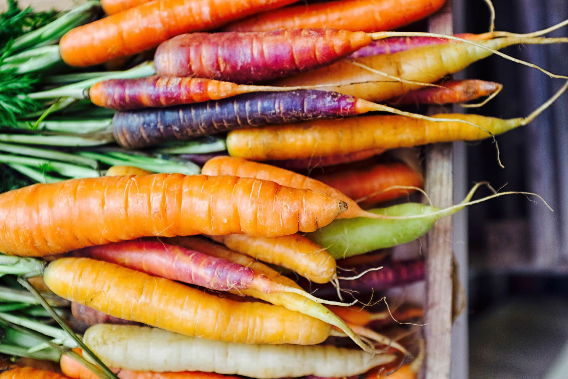 a basket full of different colored carrots.