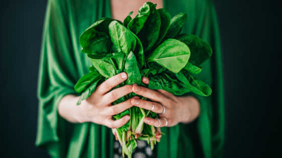 Woman holding spinach leaves.