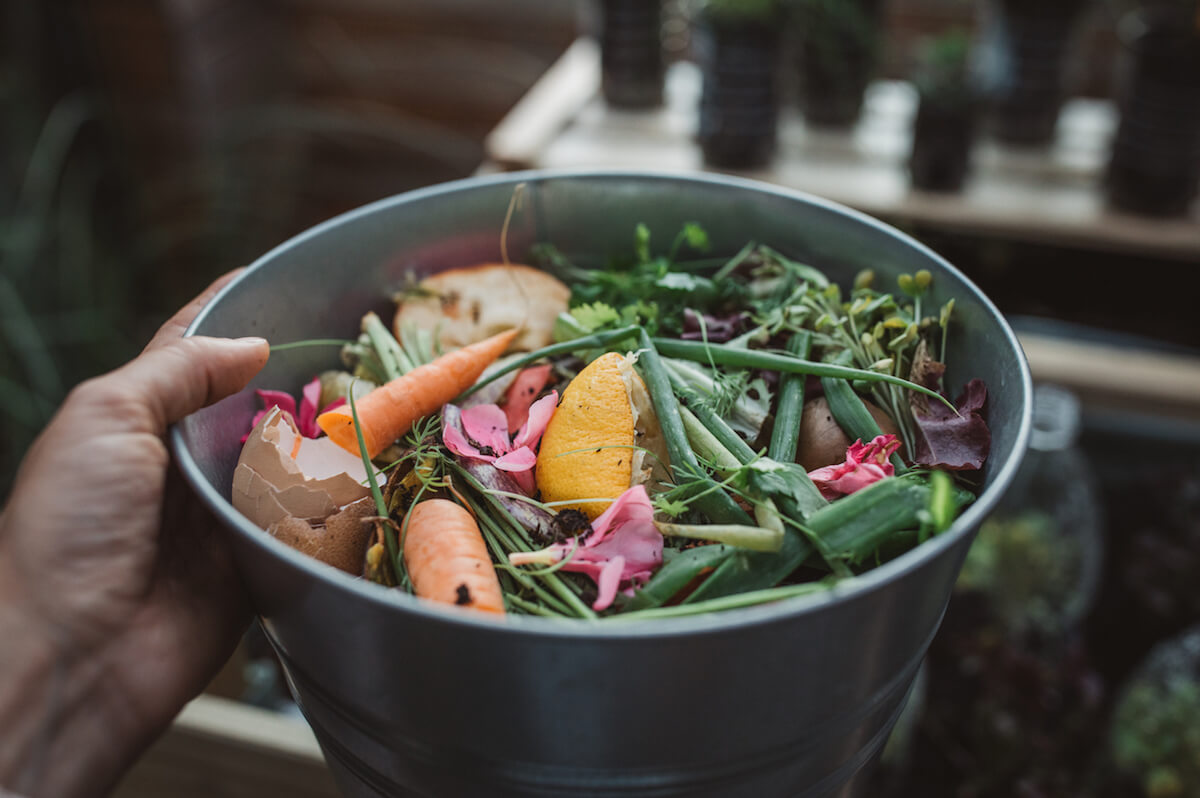 Bucket full of vegetable scraps ready to be composted.