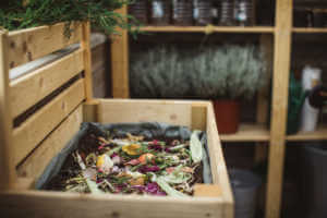 Outdoor wooden compost bin filled with kitchen scraps.