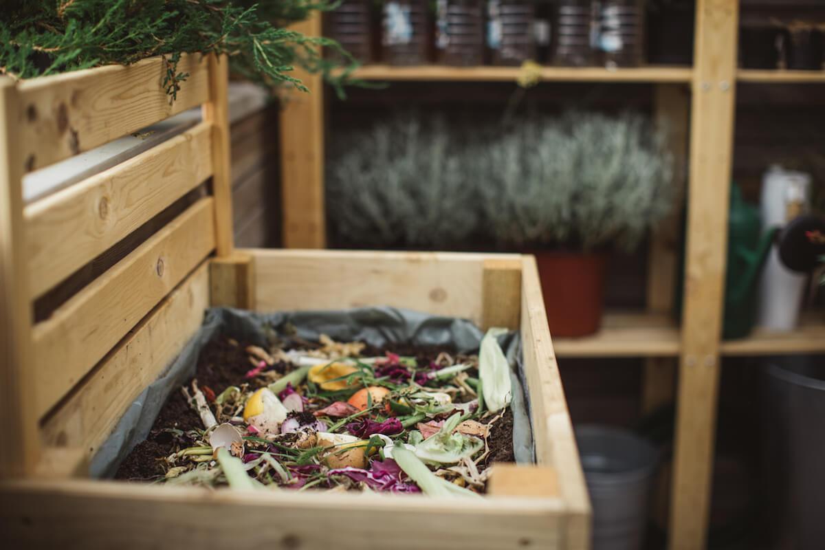Outdoor wooden compost bin filled with kitchen scraps.