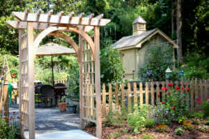 Garden entrance with fence and wooden arched trellis.