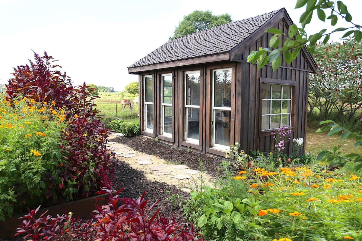 Rustic wooden greenhouse in a lush garden.