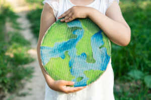Young girl holding cardboard cutout of the earth.