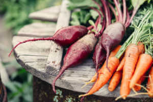 beets and carrots laying on top of round wooden table