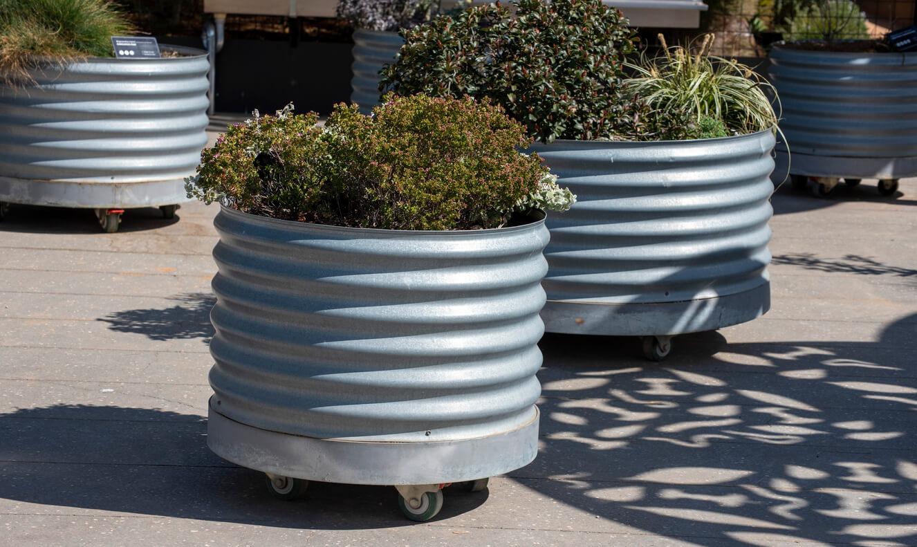 Circular metal garden beds on wheels.