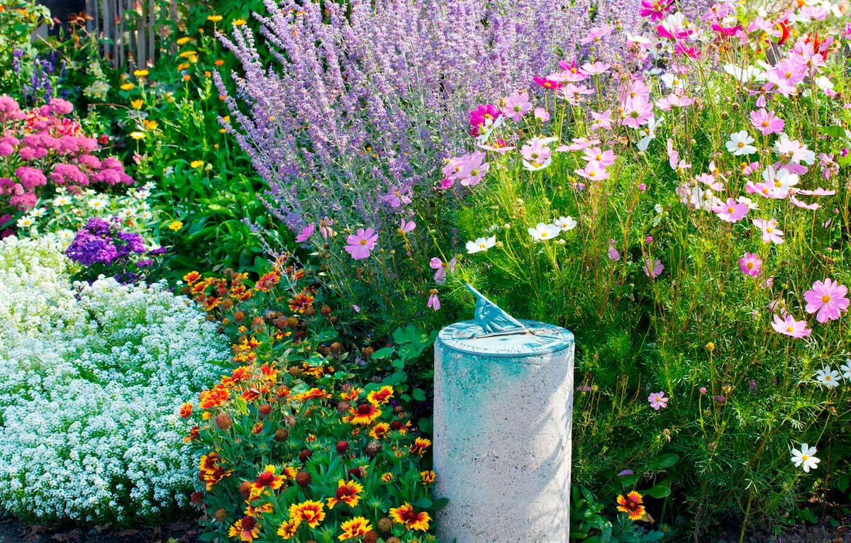 A verdigris copper sundial rests in a flower garden.