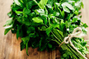 Parsley bouquet on a wooden surface.