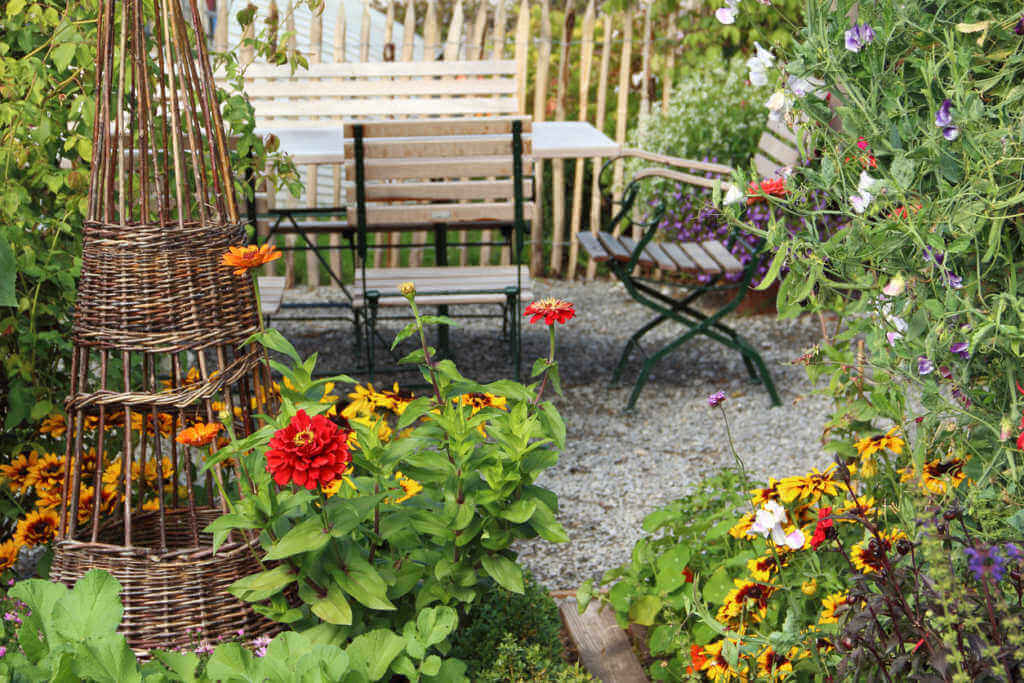 Beautiful garden with tables and chairs and flowers blooming