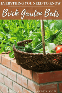a basket full of fresh vegetables on top of a brick raised garden bed.