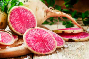 Slices of pink watermelon radish on a wooden table