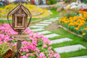 Welcome sign on colorful garden.
