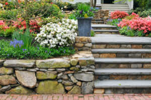 Stone wall, steps and planter on colorful, landscaped garden.