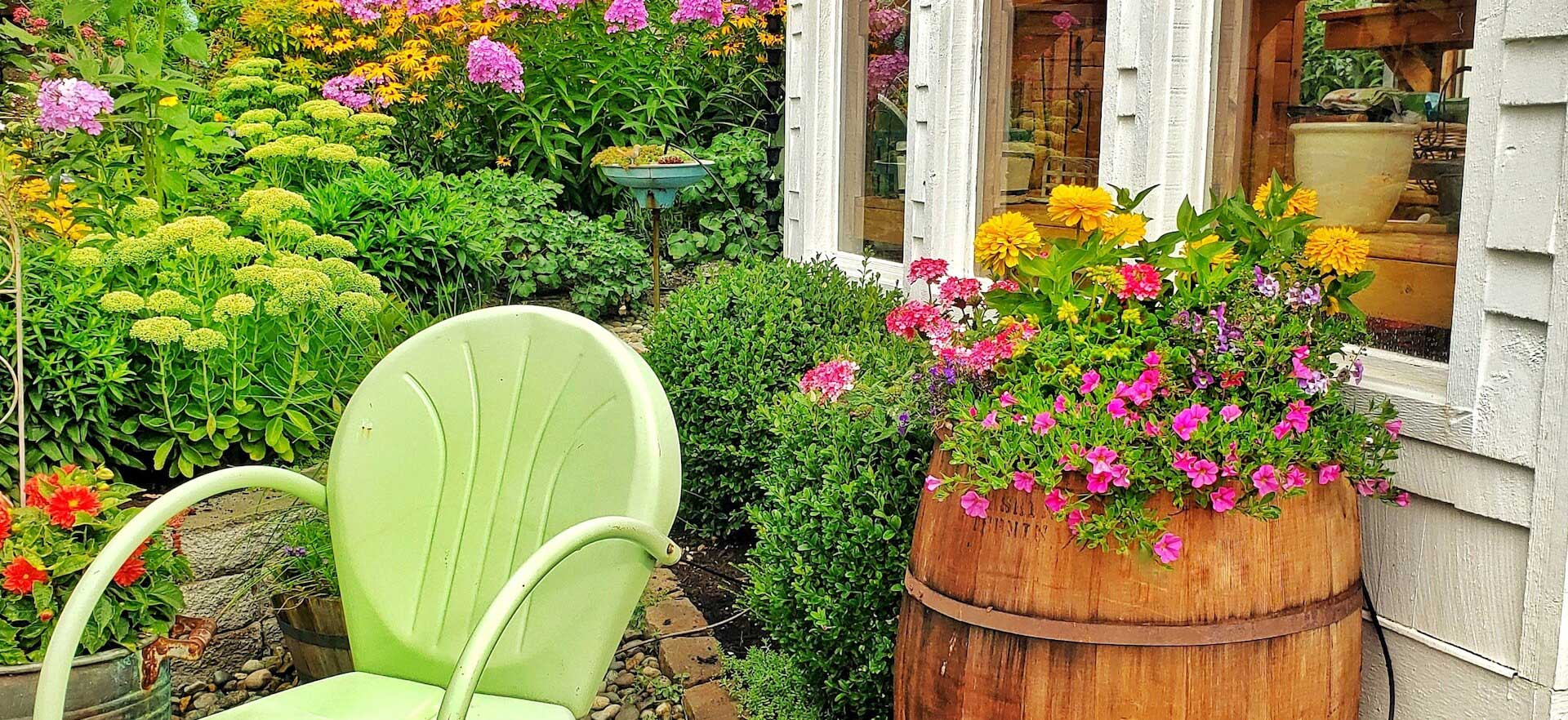 Wooden barrel flower container in front of greenhouse and lush flower garden along with a green metal chair.