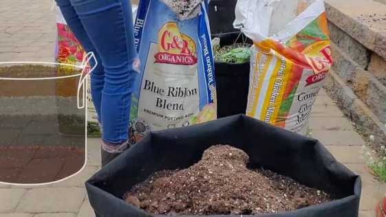 Woman surrounded by G&B organics soil and fertilizer bags adding organic material into fabric grow bag.
