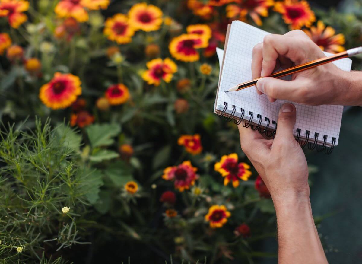 Hand taking notes by flower garden