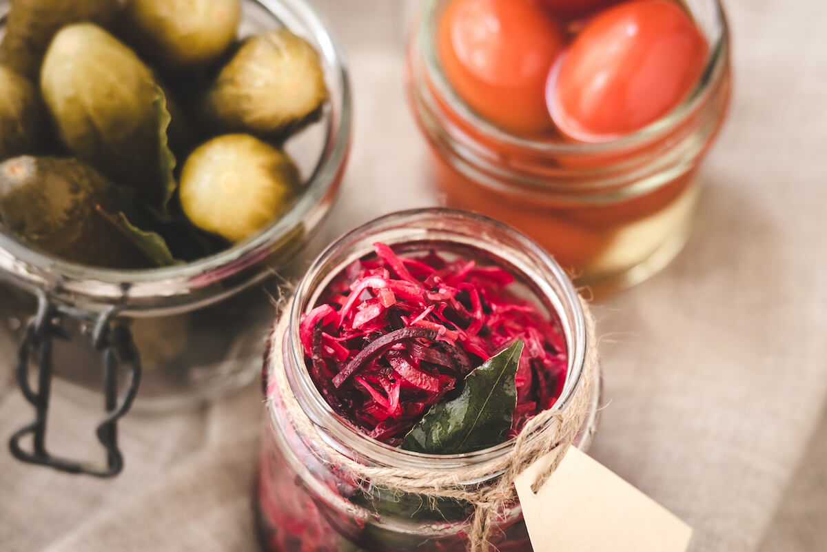 Pickled beets, tomatoes and pickles in jars.