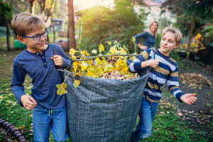 boys collecting autumn leaves in a large bag.