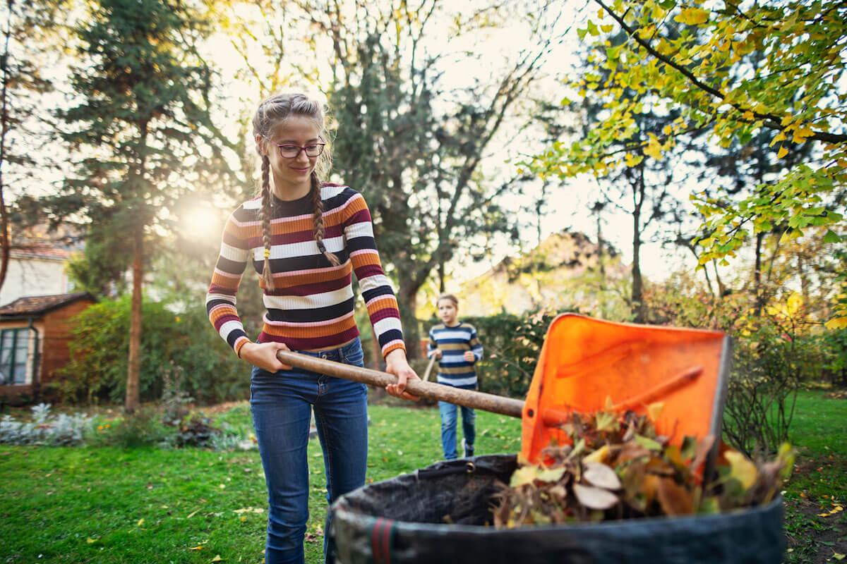 Teenage girl composting autumn leaves.