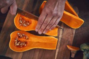 man slicing pumpkin squash