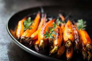 Roasted and glazed carrots on a black plate.