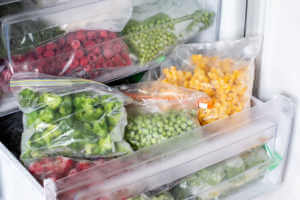 frozen bags of broccoli and other vegetables in freezer