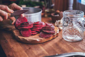 hands slicing red beets for preserving