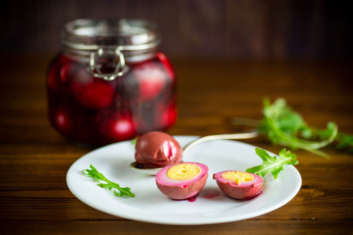 plate of marinated eggs next to glass jar of pickled beets