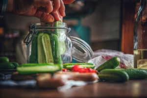 a man preserving cucumbers in a glass jar