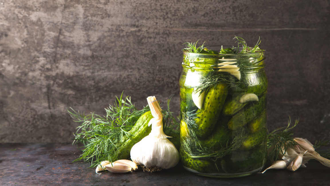 glass jar of pickles with dill and garlic